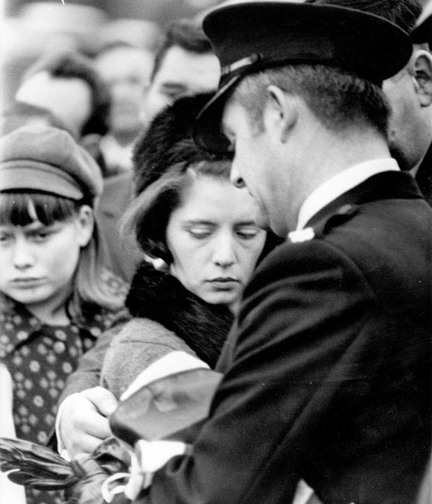 Mrs Arbuckle, wife of constable Victor Arbuckle who was shot during the Shankill Road riots receives the Union Jack which covered the coffin during the funeral service at Roselawn Cemetry
