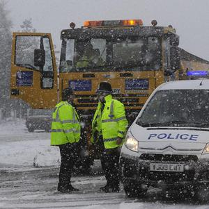 Police officers direct a gritting lorry on a road in the North Yorkshire Moors