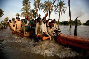 Villagers displaced from their homes by flooding travel through flood waters on the back of a truck