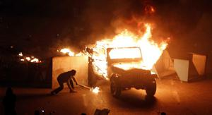 In this photo released by China's Xinhua News Agency, a police vehicle is set on fire by anti-government demonstrators in Cairo, capital of Egypt, on Friday, Jan. 28, 2011. Protesters have seized the streets of Cairo, battling police with stones and firebombs, burning down the ruling party headquarters, and defying a night curfew enforced by a military deployment.