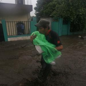 A man carries a child under heavy rains of tropical storm Agatha in Patulul, Guatemala (AP)