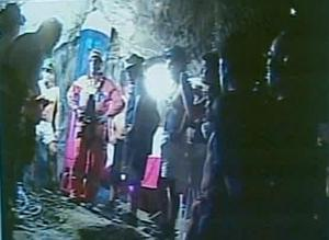 In this screen grab taken from video, rescuer Manuel Gonzalez Pavez, second left, speaks to the 33 trapped miners after being lowered into the mine near Copiapo, Chile.(AP Photo)