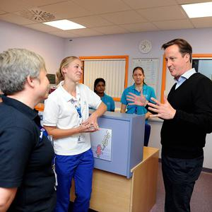 Prime Minister David Cameron chats to nurses during a visit to a hospital in Oxford where he met teenage patients and their parents