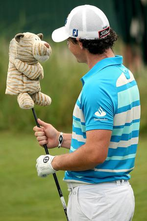 Rory McIlroy of Northern Ireland looks at Martin Kaymer's club head cover during a practice round of the 94th PGA Championship at the Ocean Course on August 8, 2012 in Kiawah Island, South Carolina