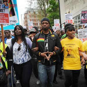 Demonstrators march in protest at the death of singer David Emmanuel also known as Smiley Culture