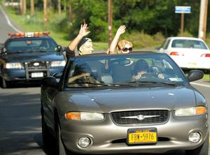A couple wearing a Bill Clinton mask and Hillary Clinton mask drive by as the town prepares for the wedding of Chelsea Clinton and Marc Mezvinsky on July 31, 2010