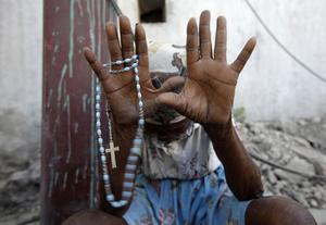 A woman prays during Mass held outside of the city's main Cathedral in Port-au-Prince, Sunday, Jan. 17, 2010