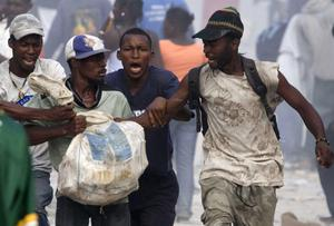 In this photo released by China's Xinhua News Agency, looters fight for a bag of materials in Haitian capital Port-au-Prince on Saturday, Jan. 16, 2010.