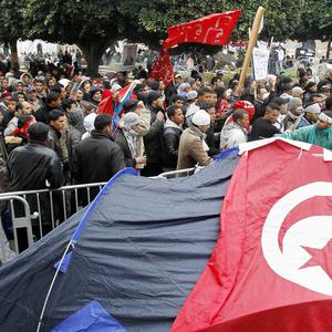 Protesters walk past a tent pitched in front of the prime minister's office in Tunis (AP)