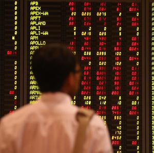 An investor looks at stock prices at a bank in Kuala Lumpur, Malaysia (AP)
