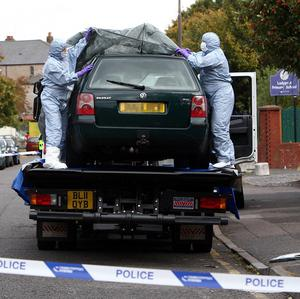Police forensic officers cover a car amid a large counter-terrorism operation in Birmingham