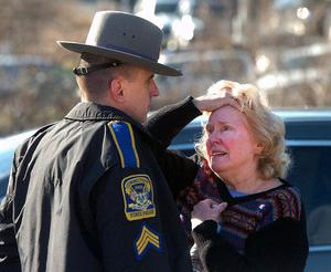 A woman speaks with a Connecticut State Police officer near Sandy Hook Elementary School, Friday, Dec. 14, 2012 in Newtown, Conn. A man killed his mother at home and then opened fire Friday inside the elementary school where she taught, massacring 26 people, including 20 children, as youngsters cowered in fear to the sound of gunshots echoing through the building and screams coming over the intercom. (AP Photo/The Hour, Alex von Kleydorff)