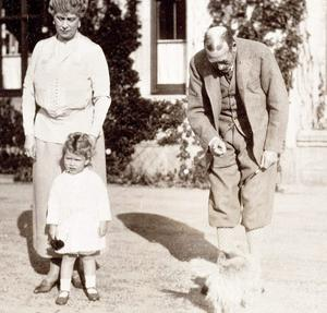 Princess Elizabeth with her grandparents King George V and Queen Mary; and Snip the King's Cairn terrier, 1928.