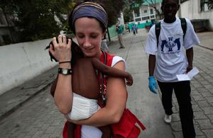 A Red Cross worker holds a baby who had been suffering from severe dehydration in the central hospital of Port-au-Prince January 19, 2010 in Port-au-Prince, Haiti.