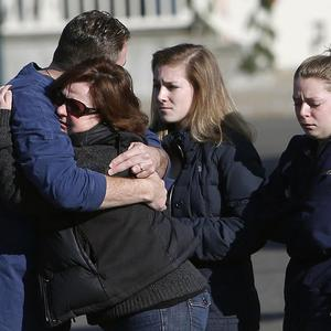Mourners embrace outside Saint Rose of Lima Roman Catholic Church in Newtown, Connecticut (AP)