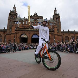 Daniel MacAskill carrying the Olympic Flame on the torch relay leg in Glasgow (Ben Birchall/LOCOG/PA)