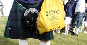 A member of the public wearing a kilt and holding a bag commemorating the State Papal visit at grounds of Bellahouston Park, Glasgow, ahead of a mass by Pope Benedict