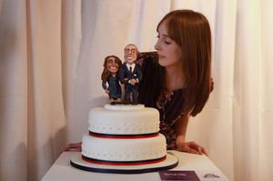 LONDON, ENGLAND - APRIL 21:  A woman admires a cake featuring Prince William and Kate Middleton at an exhibition of Royal Wedding cakes on April 21, 2011 in London, England. The cake features in the 'Let Them Eat Cake' exhibition inside Wellington Arch on Hyde Park Corner and is open to the public over Easter from April 22-25, 2011.  (Photo by Oli Scarff/Getty Images)