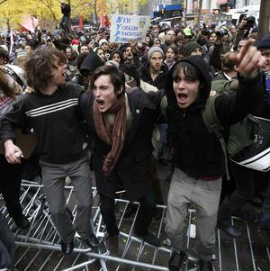 Occupy Wall Street protesters jump on police barricades in Zuccotti Park in New York (AP)