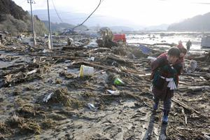 A woman, carrying a child on her back, walks over tsunami-drifted debris and mud in Rikuzentakada, Iwate Prefecture, Saturday morning, March 12, 2011 after Japan's biggest recorded earthquake slammed into its eastern coast