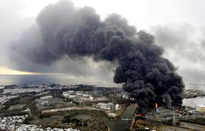 Black smoke rises from burning buildings in a factory zone in Sendai, Miyagi Prefecture, Saturday morning, March 12, 2011 after Japan's biggest recorded earthquake slammed into its eastern coast Friday