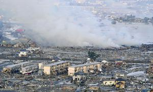 Smokes billow from an residential area in Sendai, northern Japan Saturday, March 12, 2011  after Japan's biggest recorded earthquake slammed into its eastern coast
