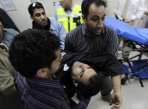Bahraini anti-government demonstrators take an injured protester to a hospital in Manama, Bahrain