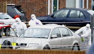 Police forensic officers examine the Police Service of Northern Ireland car at the scene of the shooting at Lismore Manor, Craigavon, Northern Ireland, Tuesday, March, 10, 2009. Irish Republican Army dissidents fatally shot a policeman in the head as he responded to an emergency call, just 48 hours after the killing of two soldiers, Northern Ireland's police commander said Tuesday. (AP Photo / Peter Morrison)