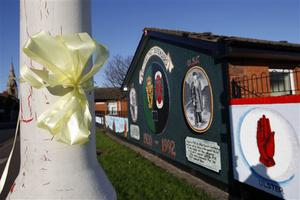A yellow ribbon calling on people to support a  British troops homecoming parade seen in near a loyalist mural East Belfast, Northern Ireland, Friday, Oct. 31, 2008.  The Royal Irish Regiment, part of the British Army, is  holding a homecoming parade Sunday after having served in Afghanistan and Iraq. Thousands of people are expected to welcome them but a  large protest by Irish Republicans opposed to British forces is planned, with security forces planning a large operation to police the area.  (AP Photo/Peter Morrison)