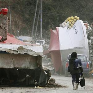 Schoolchildren bring back their school bags past vessels washed into the port town of Ofunato (AP Photo/Kyodo News)