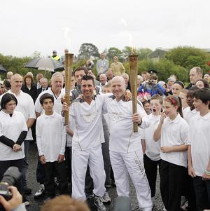 Olympic gold medal winning boxer Michael Carruth, right, receives the flame from silver medal winner Wayne McCullough on the Irish border