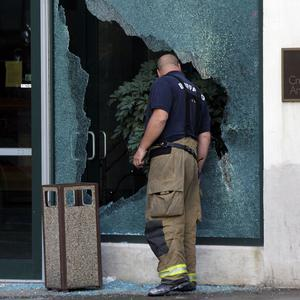 A firefighter looks through a broken window at the scene of a multiple fatal shooting in Buffalo