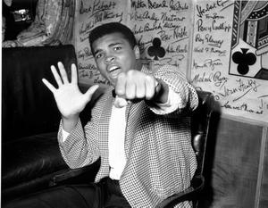 1963: Supremely confident American boxer Cassius Clay holds up five fingers in a prediction of how many rounds it will take him to knock out British boxer Henry Cooper May 27, 1963.