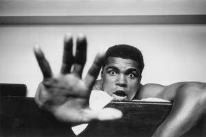 LONDON - 1963:  American Heavyweight boxer Cassius Clay (later Muhammad Ali) lying on his hotel bed May 27, 1963 in London, England. He holds up five fingers in a prediction of how many rounds it will take him to knock out British boxer Henry Cooper.