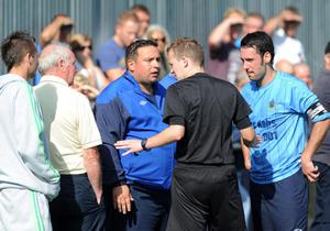 Ards Rangers manager Lee Forsythe and captain Alun Rees  protest to referee Referee Keith Kennedy who give Ards Rangers' Jamie Patterson the red card for his challenge on Ards Kyle McDowell