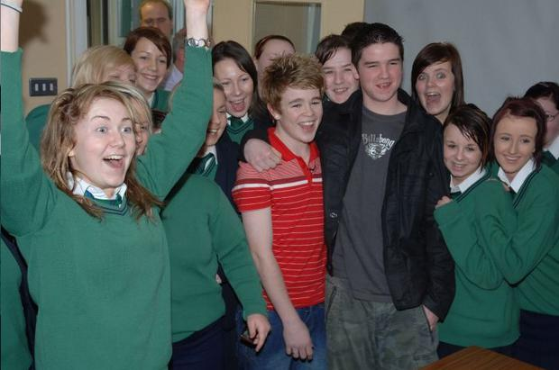 School pals mob singing star Eoghan Quigg when he came home to Dungiven yesterday to see his new baby sister Chrissie Mia