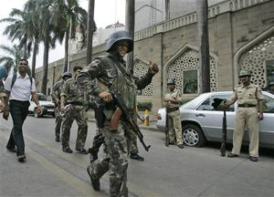 Indian commandos show the thumbs-up sign after the completion of their operation inside Taj Mahal hotel, background, in Mumbai, India, Saturday, Nov. 29, 2008. Indian commandos killed the last remaining gunmen holed up at the luxury Mumbai hotel Saturday, ending a 60-hour rampage through India's financial capital by suspected Islamic militants that killed people and rocked the nation. (AP Photo/Gurinder Osan)