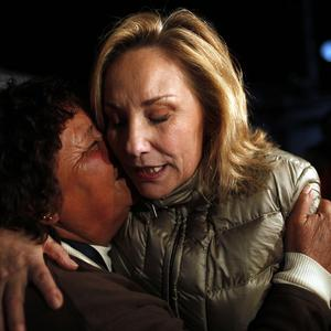 Chile's First Lady Cecilia Morel, right, embraces a relative of a trapped miner outside the San Jose mine in Copiapo, Chile (AP)