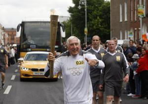 Former Olympian Ronnie Delany carrying the Olympic Flame on the Torch Relay leg through Dublin
