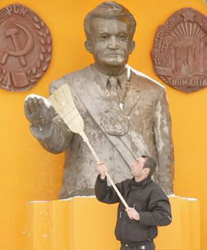A man uses a broom to remove snow from the bust of communist dictator Nicolae Ceausescu in Podari, southern Romania, 20 years after his execution in 1989.