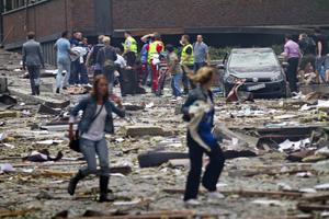 Two women are seen leaving as rescue workers arrive to help the injured following an explosion in Oslo, Norway Friday July 22, 2011