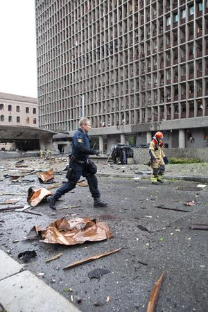 An officer responds in the centre of Oslo, Friday July 22, 2010, following an explosion that tore open several buildings including the prime minister's office, shattering windows and covering the street with documents and debris
