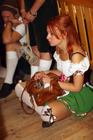 MUNICH, GERMANY - SEPTEMBER 19:  A young woman waits for the opening of the Oktoberfest beer festival on September 19, 2009 in Munich, Germany. Oktoberfest is Germany's and the world largest fair. About six million people attend the sixteen-day festival during late September and early October.  (Photo by Johannes Simon/Getty Images)