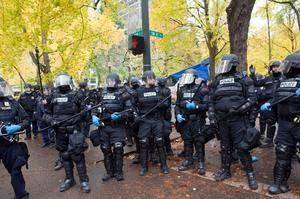 PORTLAND - NOVEMBER 13: Police in riot gear work to remove remaining protesters from the streets around the Occupy Portland encampment November 13, 2011 in Portland, Oregon. Portland police have reclaimed the two parks in which occupiers have been camping after a night of brinksmanship with protesting crowds of several thousands. (Photo by Natalie Behring/Getty Images)