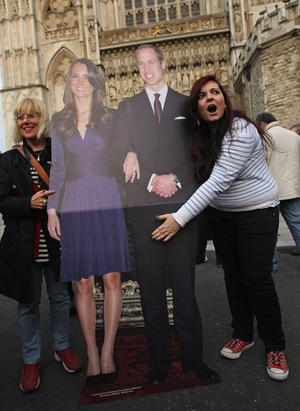 LONDON, ENGLAND - APRIL 28:  An Italian tourist extends her hand over her idea of the Royal Jewels next to a cardbaord mock up of Prince William and Kate Middleton outside Westminster Abbey a day ahead of the Royal Wedding on April 28, 2011 in London, England. Millions of people the world over are expected to watch live broadcasts of the wedding on television in what is becoming the most talked about event of the year.  (Photo by Sean Gallup/Getty Images)