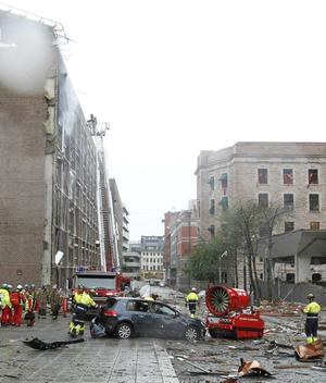 A tracked high speed mist fan is used to drag a damaged vehicle away from a building in central Oslo, Friday July 22, 2011, following an explosion that tore open several buildings including the prime minister's office, shattering windows and covering the street with documents