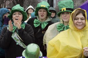 Spectators react as they brave rain and 40 degree temperatures to watch the St. Patrick's Day parade in Chicago