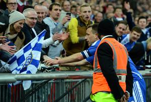 LONDON, ENGLAND - APRIL 15:  John Terry of Chelsea hands his boots to a fan after victory in the FA Cup with Budweiser Semi Final match between Tottenham Hotspur and Chelsea at Wembley Stadium on April 15, 2012 in London, England.  (Photo by Mike Hewitt/Getty Images)