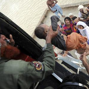 Pakistani army soldiers in a helicopter rescue families stranded by flood water in central Pakistan (AP)