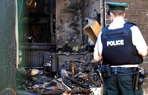 Investigation: Police examine the wreckage of the Twinbrook Social Club following yesterday morning's arson attack